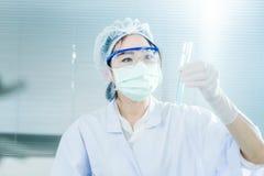 Scienziato asiatico delle donne con la provetta che fa ricerca in laboratorio clinico Immagini Stock Libere da Diritti