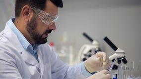 Scienziato barbuto che esegue esperimento chimico archivi video