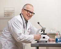Scienziato in cappotto del laboratorio con il microscopio Immagine Stock