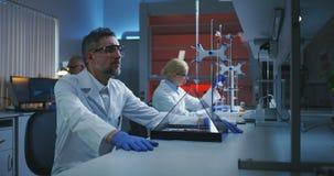 Scienziato che esamina esposizione olografica archivi video