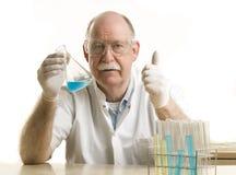 Scienziato che lavora con i prodotti chimici Immagine Stock