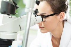 Scienziato che osserva tramite il microscopio Fotografia Stock Libera da Diritti