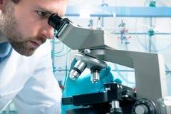 Scienziato che osserva tramite un microscopio Fotografie Stock Libere da Diritti