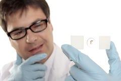 Scienziato che pensa sopra una trasparenza del microscopio immagini stock libere da diritti