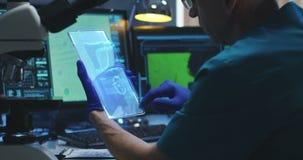Scienziato che per mezzo dello schermo di visualizzazione olografico archivi video