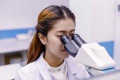 Scienziato che utilizza un microscopio in un laboratorio Immagine Stock