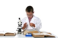 Scienziato del bambino che esamina la trasparenza del microscopio Immagine Stock