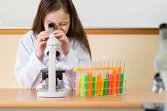 Scienziato del bambino che esamina microscopio Immagini Stock Libere da Diritti