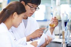 Scienziato del laboratorio di due asiatici che lavora al laboratorio con le provette immagini stock
