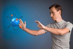 Scienziato dell'uomo con il modello atomico, concetto di ricerca Immagine Stock