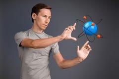 Scienziato dell'uomo con il modello atomico, concetto di ricerca Immagini Stock Libere da Diritti