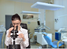 Scienziato della donna che guarda tramite il microscopio Fotografie Stock