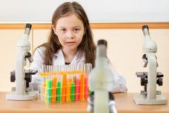 Scienziato della ragazza con il microscopio e le provette nella scienza l Immagini Stock