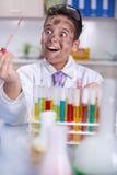 Scienziato divertente di Yong che fa un certo esperimento pazzo Immagine Stock Libera da Diritti