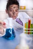 Scienziato divertente di Yong che fa un certo esperimento pazzo Immagini Stock