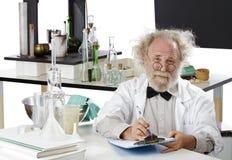 Scienziato eccentrico in appunti della holding del laboratorio immagini stock