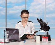 Scienziato femminile che legge un libro Fotografie Stock