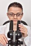 Scienziato femminile che osserva tramite il microscopio Fotografia Stock Libera da Diritti