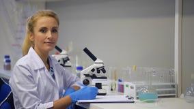 Scienziato femminile che posa per la macchina fotografica mentre lavorando nel laboratorio stock footage
