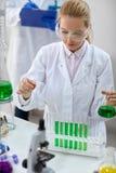 Scienziato femminile con la pipetta ed i tubi che fanno prova Immagini Stock