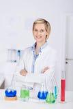 Scienziato femminile sicuro With Arms Crossed che sta allo scrittorio Immagine Stock