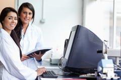 Scienziato femminile sorridente che propone con un video Immagini Stock