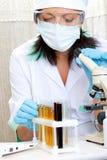 Scienziato in laboratorio che analizza liquido giallo in provetta Fotografia Stock