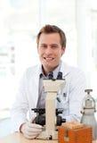 Scienziato maschio che osserva tramite un microscopio Fotografie Stock