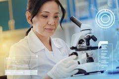 Scienziato professionista che sembra calmo mentre lavorando con un microscopio fotografia stock