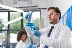 Scienziato serio Looking At Flask con liquido blu in laboratorio sopra il gruppo di fabbricazione scientifica dei ricercatori immagini stock