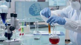 Scienziato in tuta che prende le sonde da liquido colorato stock footage