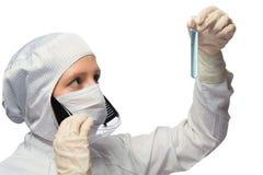 scienziato in un vestito protettivo ed in una maschera bianchi, vetri trasparenti protettivi dei vestiti e studi una provetta con fotografia stock libera da diritti