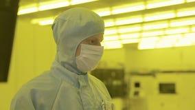 Scienziato in vestiti sterili, maschera dell'ingegnere sia in una zona pulita che esamina un processo tecnologicamente ha avanzat video d archivio