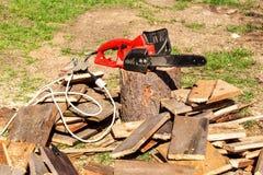 Scies et tronçonneuse électriques Électrique a vu la chaîne sur le fond du bois de construction scié Le concept de traiter le boi Image stock