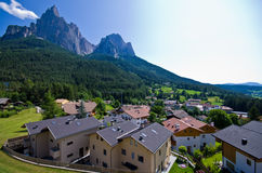 The Sciliar seen from Alpe di Siusi. The Sciliar mountain range seen from Alpe di Siusi cemetery, residential buildings in the foreground Royalty Free Stock Images