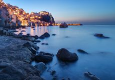 Scilla in Calabria, Italy at dusk. Scilla, in Calabria, southern Italy, is a small, picturesque, fishing village. Here seen at dusk with sea on foreground stock photo
