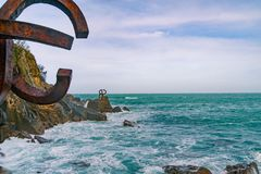 Sculpture `The Comb of the Wind` in Donostia, the Basque Country of Spain. Scilpture `The Comb of the Wind` with giant scenic waves  at the western end of the Royalty Free Stock Photos
