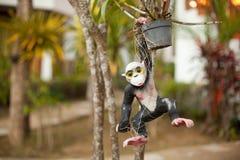 scimmia ceramica del giocattolo che appende su un vaso da fiori Fotografia Stock