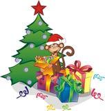 Scimmia divertente con i contenitori di regalo vicino all'albero di Natale Immagini Stock Libere da Diritti