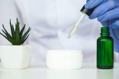 Scin-Sorgfalt Wissenschaftlerhände, die Beschaffenheit von Schönheitsprodukten prüfen lizenzfreie stockfotografie