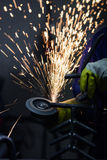 Scintille calde che volano mentre il lavoratore sta frantumando il tubo d'acciaio con una sega circolare Immagini Stock