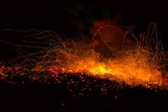 Scintille dall'esplosione dei tizzoni del fuoco su un fondo nero Immagine Stock