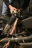 Scintille di metallo bianco calde dalla smerigliatrice che rimbalza fuori dalla struttura della bici Immagine Stock