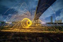 Scintille dorate calde che volano dall'uomo che fila l'ONU bruciante della lana d'acciaio Immagini Stock Libere da Diritti