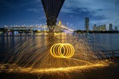 Scintille dorate calde che volano dall'uomo che fila l'ONU bruciante della lana d'acciaio Fotografie Stock Libere da Diritti