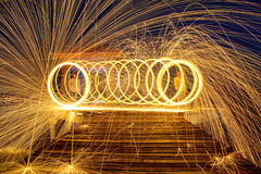 Scintille dorate calde che volano dall'uomo che fila lana d'acciaio bruciante Fotografia Stock