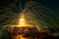 Scintille dorate calde che volano dall'uomo che fila lana d'acciaio bruciante dentro Fotografia Stock