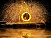 Scintille dorate calde che volano dall'uomo che fila lana d'acciaio bruciante sopra Fotografia Stock Libera da Diritti