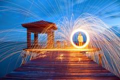 Scintille dorate calde che volano dall'uomo che fila lana d'acciaio bruciante sopra Fotografie Stock Libere da Diritti