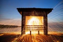 Scintille dorate calde che volano dall'uomo che fila lana d'acciaio bruciante sopra Immagini Stock